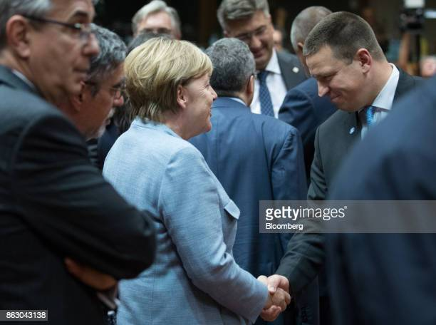Angela Merkel Germany's chancellor center shakes hands with Juri Ratas Estonia's prime minister ahead of roundtable talks with European Union leaders...