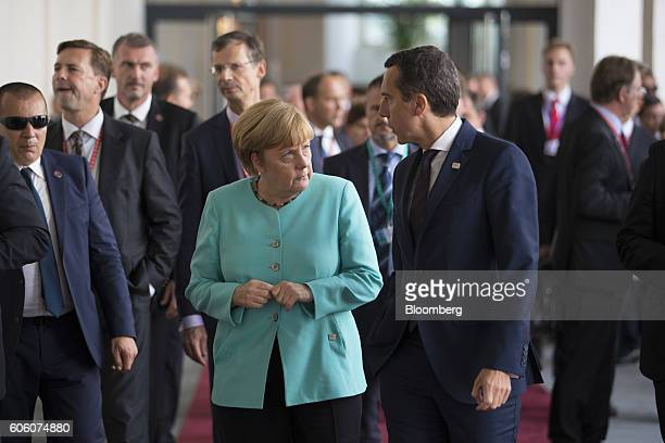 Angela Merkel Germany's chancellor center speaks with Christian Kern Austria's chancellor as they depart the morning working session during a meeting...