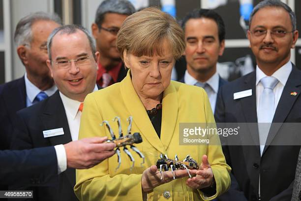 Angela Merkel Germany's chancellor holds a robotic ant manufactured by Festo KG as she visits the company's exhibition stand at the Hanover...
