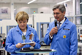 Angela Merkel Germany's chancellor is presented with a printed circuit board themed gift as Joe Kaeser chief executive officer of Siemens AG speaks...
