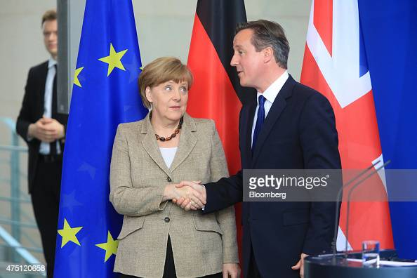 Angela Merkel Germany's chancellor left and David Cameron UK prime minister shake hands during a news conference at the Chancellery in Berlin Germany...