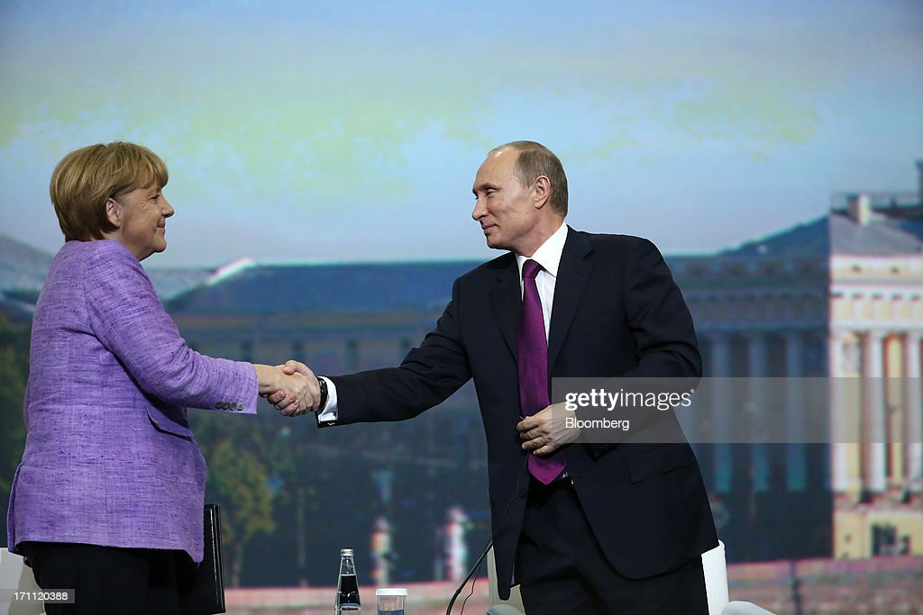 Angela Merkel, Germany's chancellor, left, shakes hands with Vladimir Putin, Russia's president, during a conference session on day two of the St. Petersburg International Economic Forum 2013 (SPIEF) in St. Petersburg, Russia, on Friday, June 21, 2013. Putin is battling investor skepticism to woo foreign executives descending on his hometown today as Russia's economy faces a risk of recession and a crackdown on critics scares off intellectuals. Photographer: Andrey Rudakov/Bloomberg via Getty Images