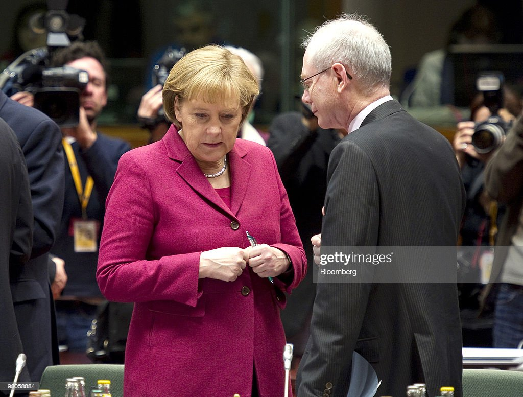 Angela Merkel, Germany's chancellor, left, stands with Herman Van Rompuy, president of the European Council, right, as EU leaders gather for the European Union Summit in Brussels, Belgium, on Friday, March 26, 2010. French President Nicolas Sarkozy capped a week of reversals with his acceptance of German demands on a contingency plan to aid Greece. Photographer: Jock Fistick/ Bloomberg