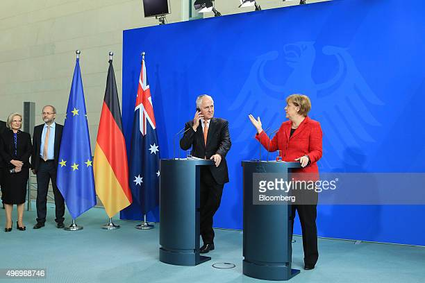 Angela Merkel Germany's chancellor right gestures as she speaks as Malcolm Turnbull Australia's prime minister adjusts his earpiece during a news...