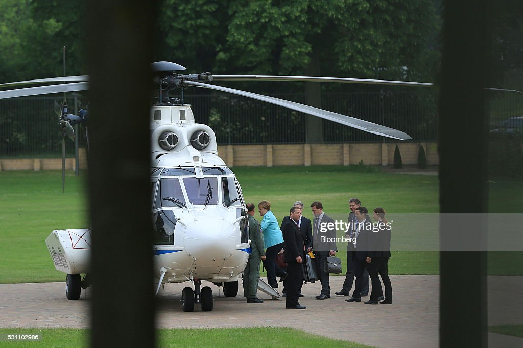 Angela Merkel, Germany's chancellor, second left, boards a helicopter as she departs a news conference following a two-day cabinet retreat in Meseburg, Germany, on Wednesday, May 25, 2016. In the latest response to the refugee crisis that's dogged Merkel since last summer, her cabinet on Wednesday backed legislation that includes stricter requirements for asylum seekers to integrate into German society. Photographer: Krisztian Bocsi/Bloomberg via Getty Images *** Angela Merkel