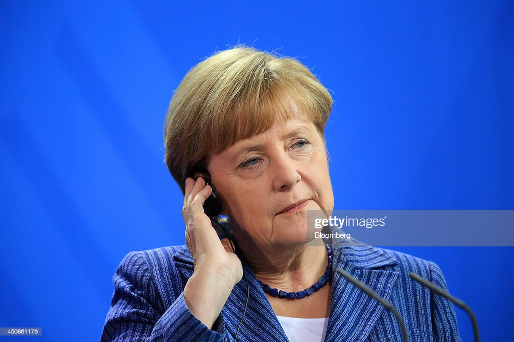 Angela Merkel Germany's chancellor wears an earpiece during a news conference at the Chancellery in Berlin Germany on Thursday June 19 2014 Merkel...