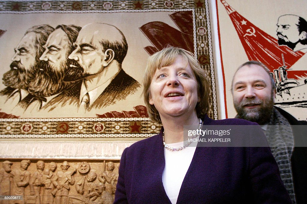 Angela Merkel leader of Germany's main opposition Christian Democratic Union party and Guenter Nooke a spokesman of her party walk past the portraits...