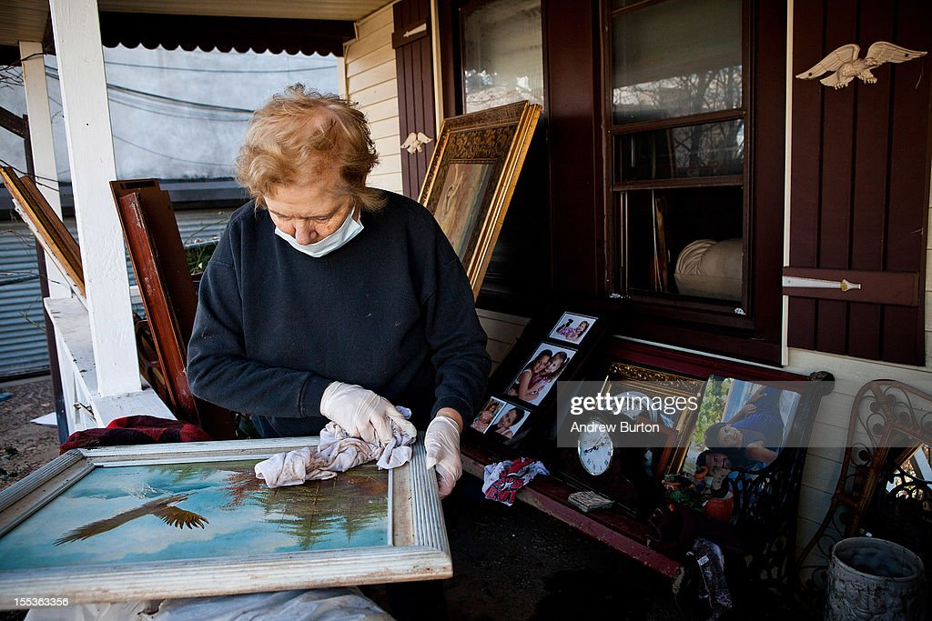 Angela Troia wipes off a painting damaged by Superstorm Sandy in the Midland Beach neighborhood of Staten Island on November 3, 2012 in New York City. As clean up efforts from Superstorm Sandy continue, colder weather and another storm predicted for next week are beginning to make some worried.