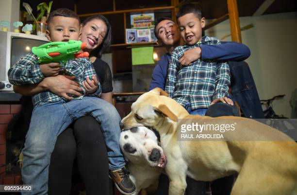 Angeles Borda a 32yearold Colombian woman who survived an acid attack ten years ago sits with her husband Juan Piedrahita their sons and their dogs...