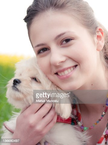 Angelic adolescent face with dog in her arms
