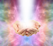 Healer's cupped hands filled up with a shaft of white energy on a misty pale multi-coloured energy formation background