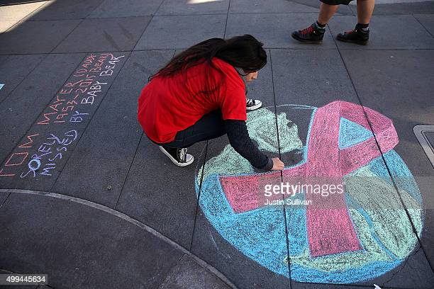 Angelica Tome does a chalk drawing of a red AIDS ribbon on Castro Street on December 1 2015 in San Francisco California To commemorate World AIDS day...