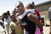 Angelina a 26yearold mother of two carries one of her children on her back as she flees from her violence ridden neighborhood in the Mathare slum of...
