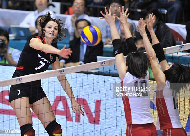 Angelina Grün of Germany attacks against Japanese players Nana Iwasaka and Risa Shinnabe during their match at the World Cup women's volleyball...