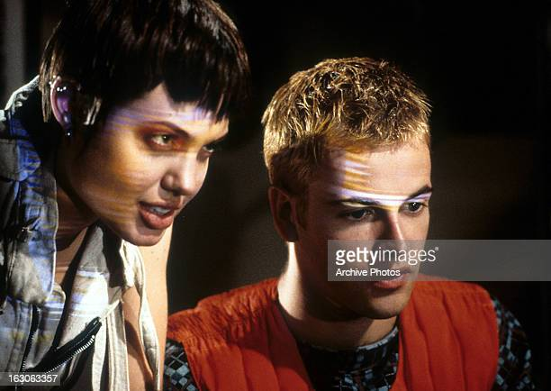 Angelina Jolie stands behind Jonny Lee Miller in a scene from the film 'Hackers' 1995