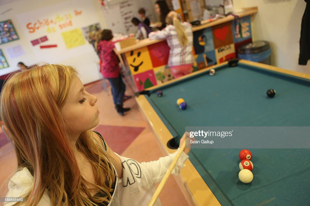 Angelina (L), 11, plays pool at the 'Arche' youth center in Marzahn-Hellersdorf district on October 5, 2012 in Berlin, Germany. The Arche (which means Ark) is a Christian-based facility that provides children of all ages with a hot lunch, help with homework, arts and play facilities and in general a welcome place to come to in Marzahn-Hellersdorf district in east Berlin, a district with high levels of unemployment and social problems. An employee said up to 90% of the children come from challenged families and that many arrive at Arche illiterate.
