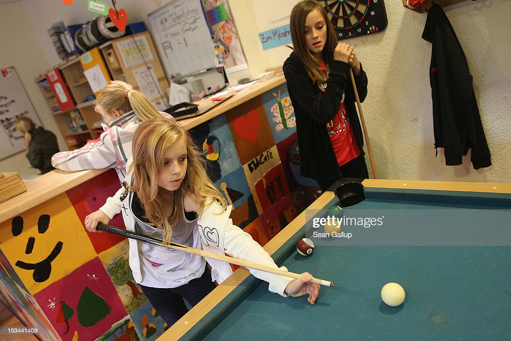 Angelina (L), 11, plays pool with Lisa, 10, at the 'Arche' youth center in Marzahn-Hellersdorf district on October 5, 2012 in Berlin, Germany. The Arche (which means Ark) is a Christian-based facility that provides children of all ages with a hot lunch, help with homework, arts and play facilities and in general a welcome place to come to in Marzahn-Hellersdorf district in east Berlin, a district with high levels of unemployment and social problems. An employee said up to 90% of the children come from challenged families and that many arrive at Arche illiterate.