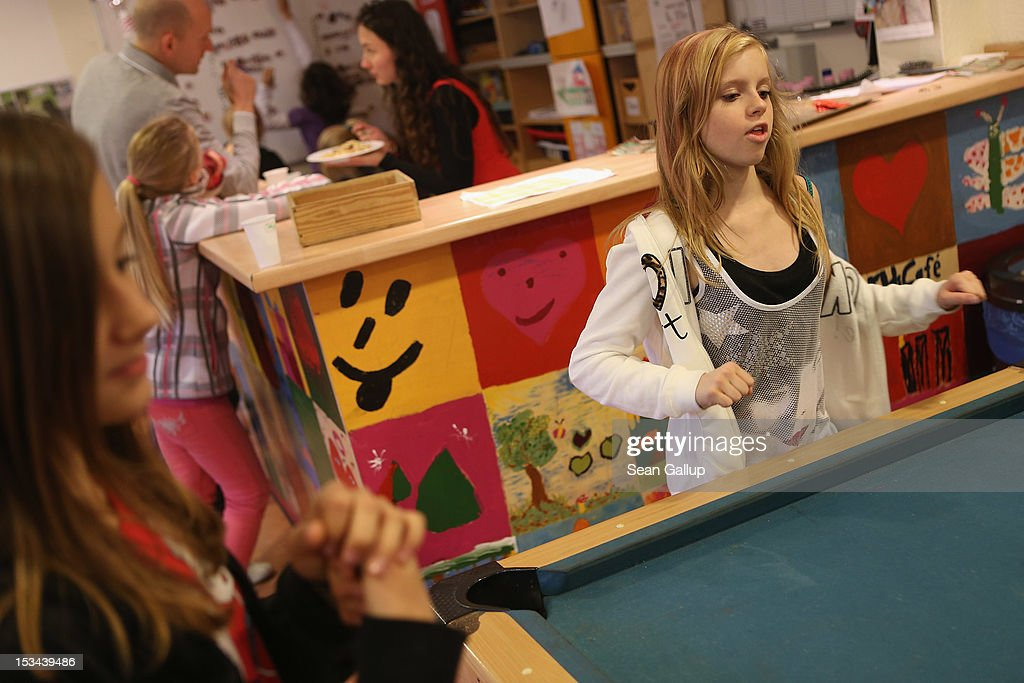 Angelina (R), 11, sings while playing pool with Lisa, 10, at the 'Arche' youth center in Marzahn-Hellersdorf district on October 5, 2012 in Berlin, Germany. The Arche (which means Ark) is a Christian-based facility that provides children of all ages with a hot lunch, help with homework, arts and play facilities and in general a welcome place to come to in Marzahn-Hellersdorf district in east Berlin, a district with high levels of unemployment and social problems. An employee said up to 90% of the children come from challenged families and that many arrive at Arche illiterate.