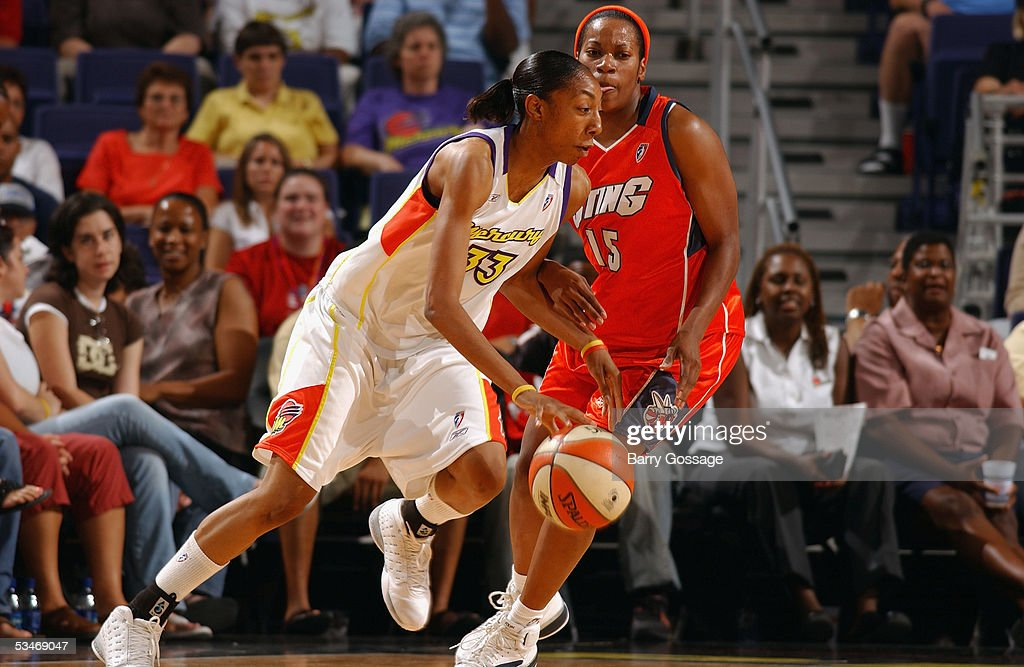 Angelina Williams of the Phoenix Mercury drives around Jia Perkins of the Charlotte Sting during a WNBA game at America West Arena on July 13 2005 in...