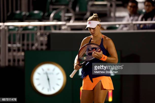 Angelique Kerber of Germany adjusts her racquet between points while playng YingYing Duan of China during the Miami Open at the Crandon Park Tennis...