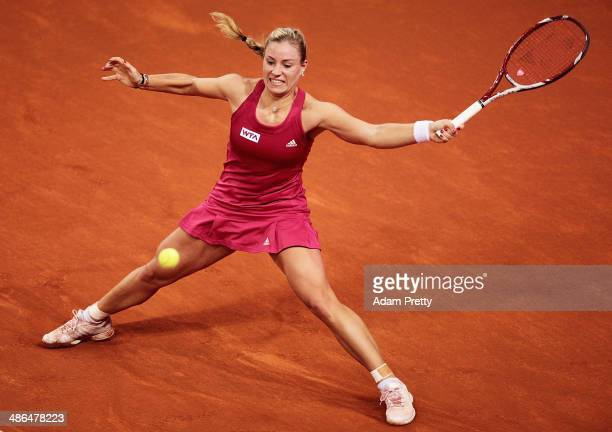 Angelique Kerber of Germany hits a forehand during her match against Carla Suarez Navarro of Spain on day four of the Porsche Tennis Grand Prix 2014...