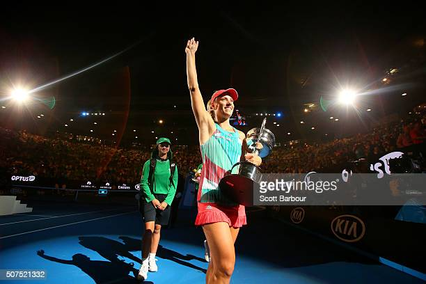Angelique Kerber of Germany holds the Daphne Akhurst Trophy and waves to the crowd at Rod Laver Arena after winning the Women's Singles Final against...
