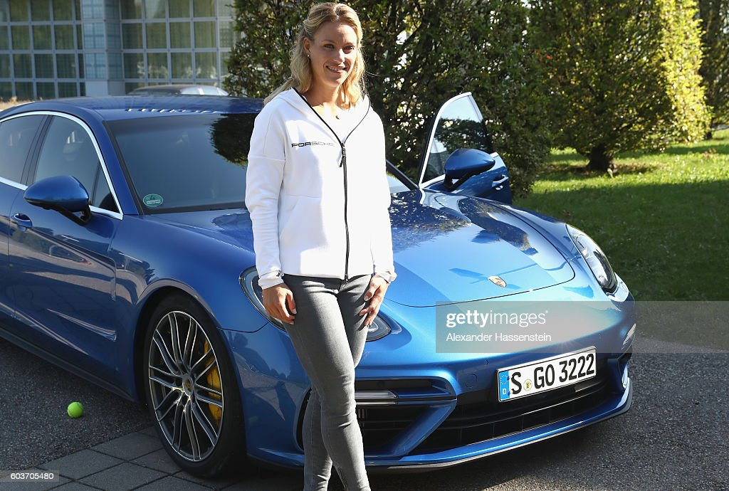 Angelique Kerber of Germany poses in front of a new Porsche Panamera Turbo after returning as new Tennis World number One and winner of the US Open at Munich Airport on September 13, 2016 in Munich, Germany.