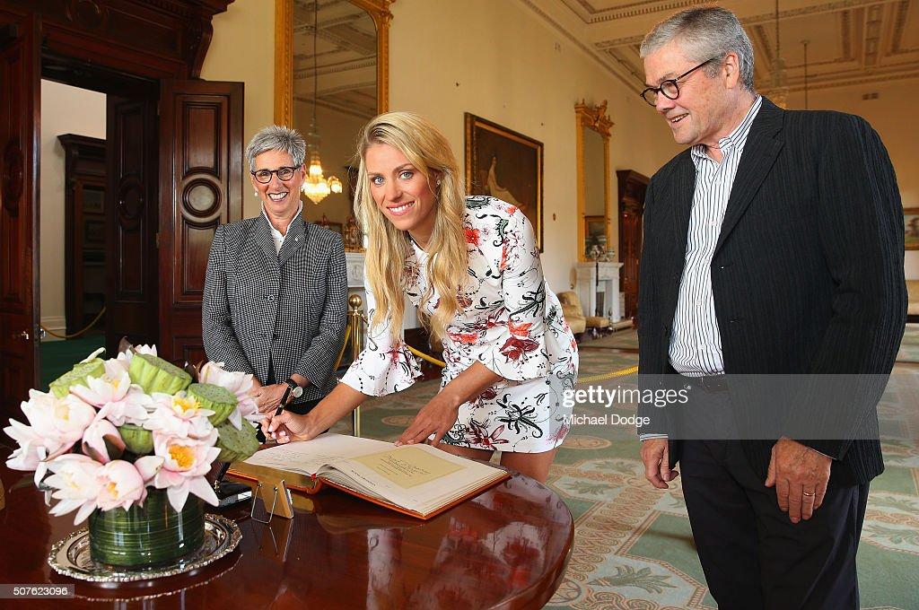 Angelique Kerber of Germany signs a book alongside Governor Of Victoria, the Honourable Linda Dessau AM, and her husband Judge Anthony Howard during a photocall at Government House after winning the 2016 Australian Open on January 31, 2016 in Melbourne, Australia.