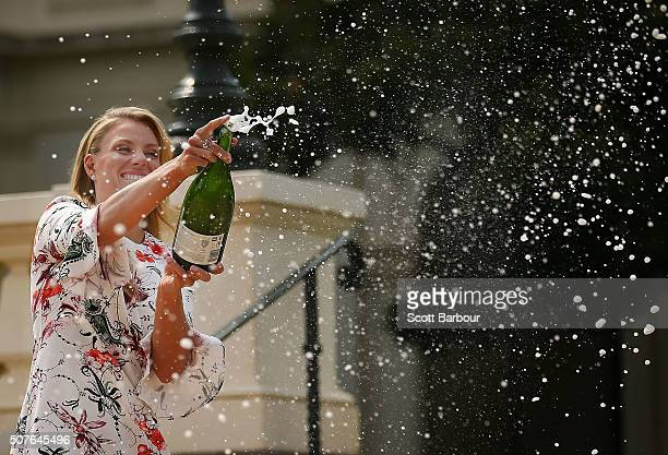 Angelique Kerber of Germany sprays champagne as she poses with the Daphne Akhurst Memorial Cup during a photocall at Government House after winning...