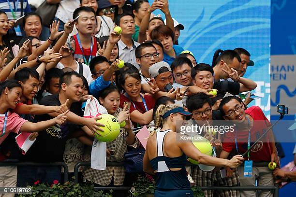 Angelique Kerber of Germany take a selfie with spectators after defeating Kristina Mladenovic of France during their third round match on Day three...