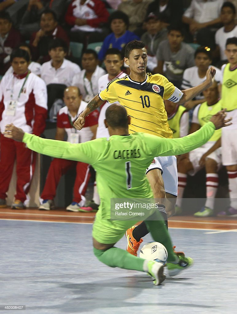 Angello Caro of Colombia fights for the ball with Edson Caceres of Peru during a match between Colombia and Peru as part of the XVII Bolivarian Games Trujillo 2013 at Videna San Luis on November 25, 2013 in Lima, Peru.