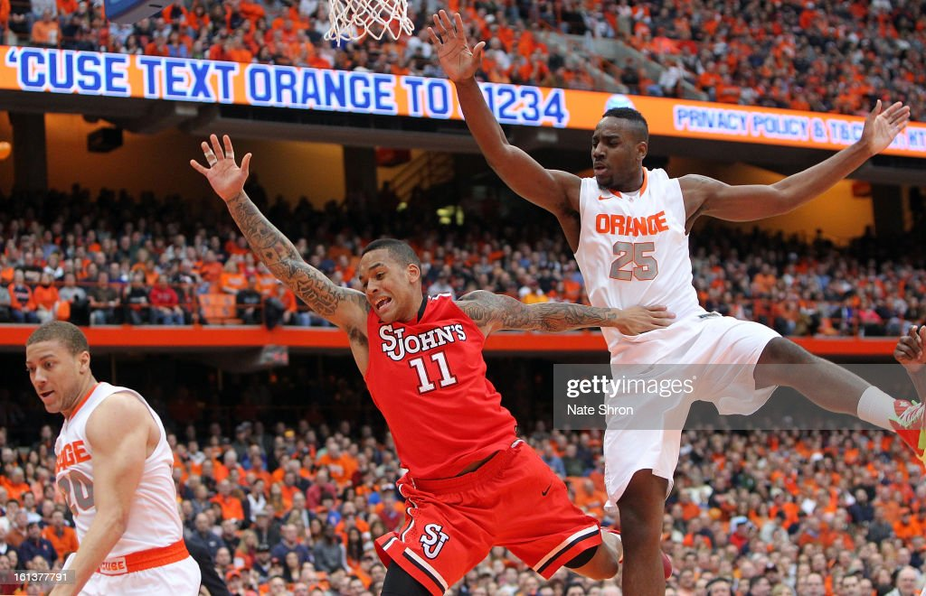 D'Angelo Harrison #11 of the St. John's Red Storm and Rakeem Christmas #25 of the Syracuse Orange fall as they reach for a rebound during the game at the Carrier Dome on February 10, 2013 in Syracuse, New York.