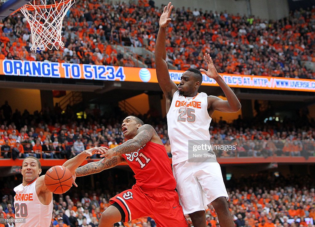 D'Angelo Harrison #11 of the St. John's Red Storm drives to the basket against Brandon Triche #20 and Rakeem Christmas #25 of the Syracuse Orange during the game at the Carrier Dome on February 10, 2013 in Syracuse, New York.