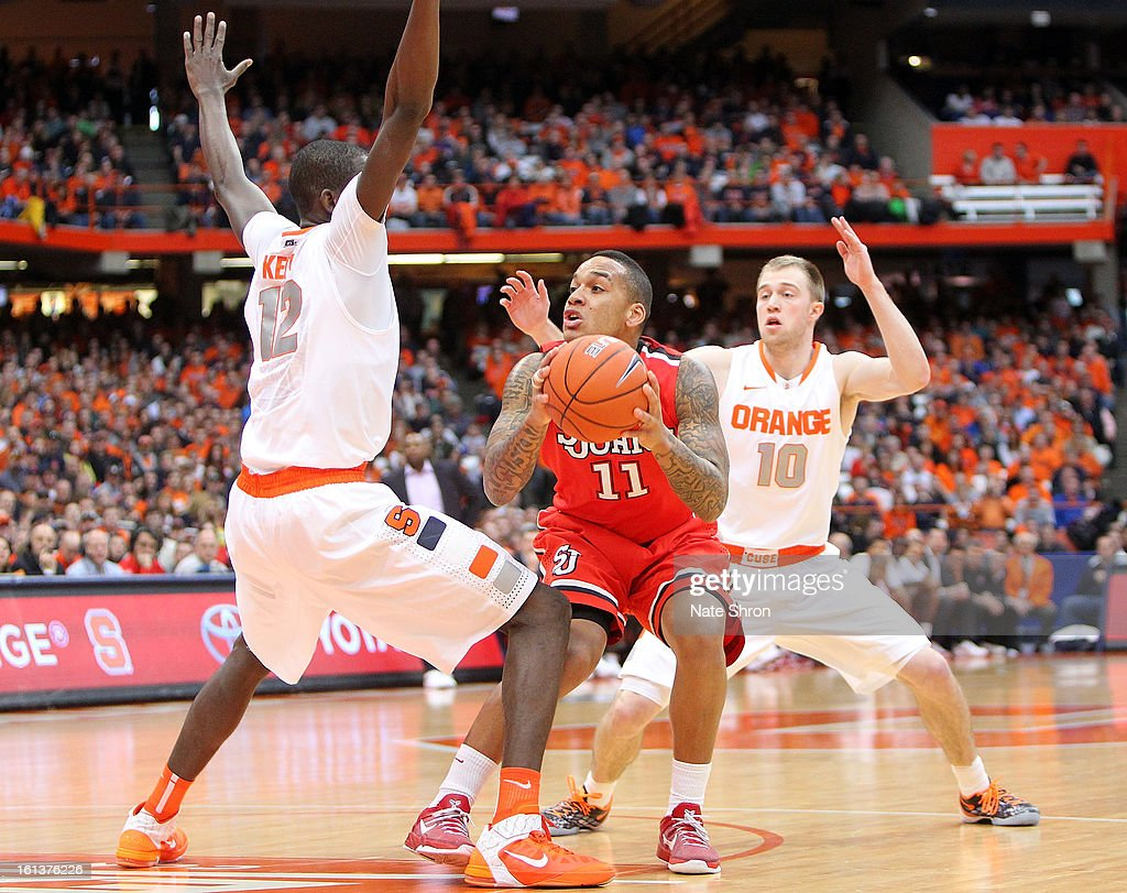 D'Angelo Harrison #11 of the St. John's Red Storm drives to the basket against Baye Moussa Keita #12 and Trevor Cooney #10 of the Syracuse Orange during the game at the Carrier Dome on February 10, 2013 in Syracuse, New York.