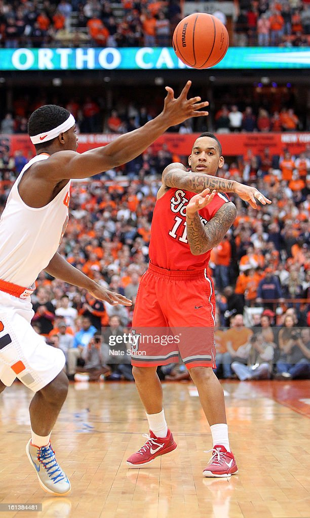 D'Angelo Harrison #11 of the St. John's Red Storm passes the ball against C.J. Fair #5 of the Syracuse Orange during the game at the Carrier Dome on February 10, 2013 in Syracuse, New York.