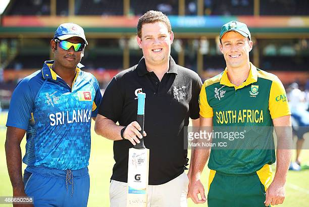 Angelo Mathews of Sri Lanka and AB De Villiers of South Africa pose for a photo with the Pepsi coin toss winner before the 2015 ICC Cricket World Cup...