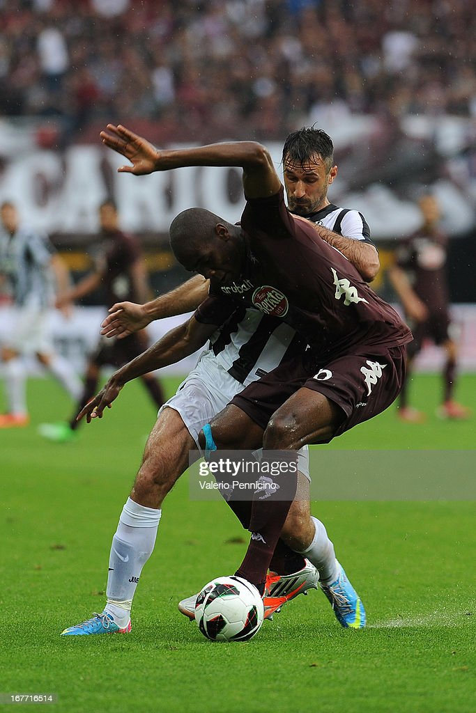 Angelo Ogbonna (L) of Torino FC is challenged by Mirko Vucinic of Juventus during the Serie A match between Torino FC and Juventus at Stadio Olimpico di Torino on April 28, 2013 in Turin, Italy.
