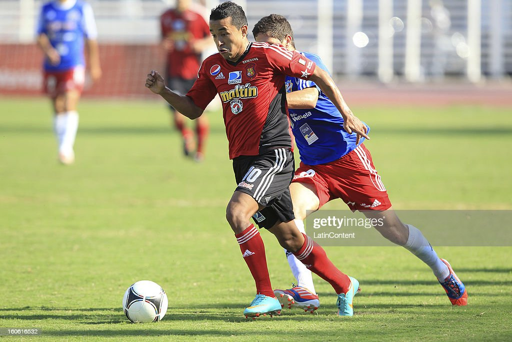Angelo Pena (L) of Caracas FC struggles for the ball with Gianfranco Di Julio (R) of Atletico Venezuela during a match between Caracas FC and Atletico Venezuela as part of the Torneo Clausura 2013 at Brigido Iriarte Stadium on February 03, 2013 in Caracas, Venezuela.