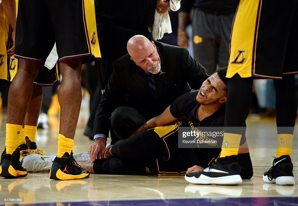 D'Angelo Russell #1 of the Los Angeles Lakers grimaces in pain after injuring his right ankle as team athletic trainer Gary Vitti looks on during the basketball game against Denver Nuggets at Staples Center March 25, 2016, in Los Angeles, California.