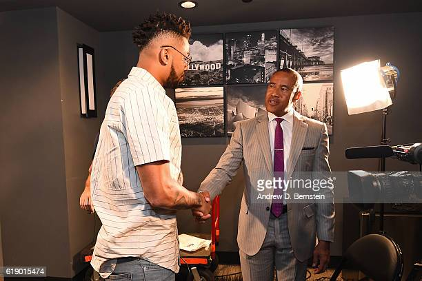 Angelo Russell of the Los Angeles Lakers shakes hands with ESPN NBA Analyst Mark Jones during and interview before the game against the Houston...