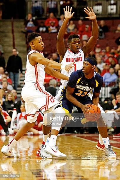 Angelo Russell of the Ohio State Buckeyes and Jae'Sean Tate of the Ohio State Buckeyes guard JaJuan Johnson of the Marquette Golden Eagles during the...