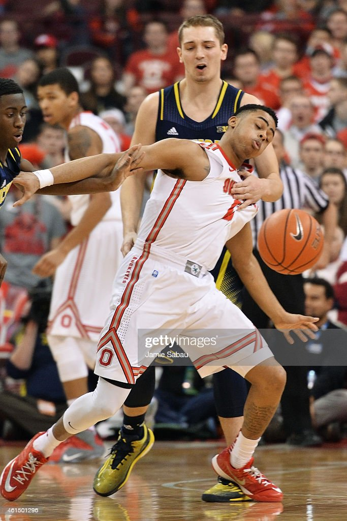 Angelo Russell of the Ohio State Buckeyes is fouled as he and Mark Donnal of the Michigan Wolverines chase after a loose ball in the second half on...