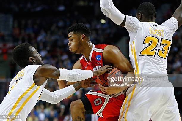 Angelo Russell of the Ohio State Buckeyes tries to elude JeQuan Lewis and teammate Jarred Guest of the Virginia Commonwealth Rams in the first half...