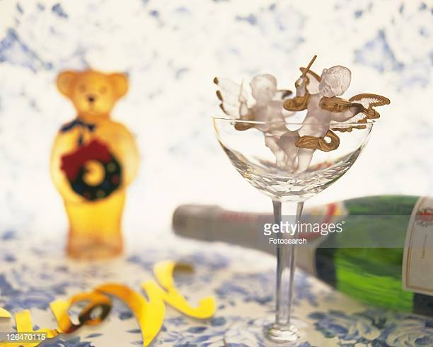 Angels in glass with teddy bear and champagne bottle, front view