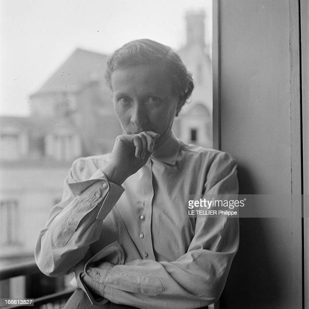 Angers A Angers dans un appartement portrait d'une femme non identifiée posant dans l'encadrement d'une fenêtre une main contre sa bouche