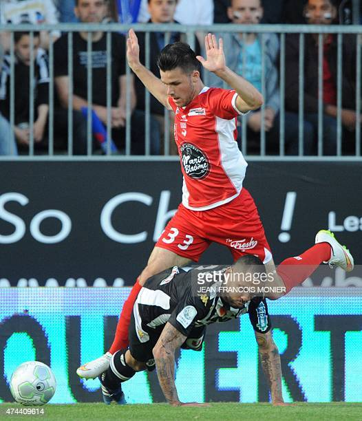 Angers' French defender Gael Angoula vies for the ball with Nimes' French midfielder Antonin Bobichon during the French L2 football match between...