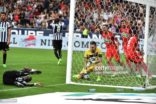 Angers' French defender Issa Cissokho falls as Angers' French goalkeeper Alexandre Letellier and Paris SaintGermain's players react after he scored...