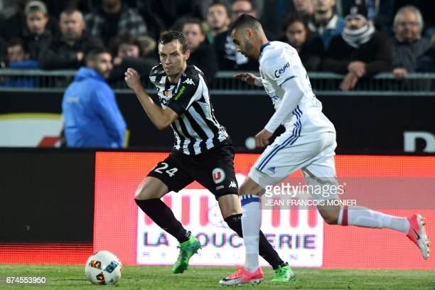 Angers' French defender Romain Thomas vies for the ball with Lyon's French Algerian midfielder Rachid Ghezzal during the French L1 football match...