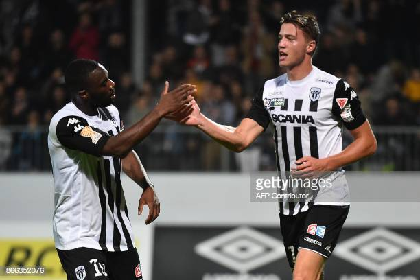 Angers' French forward Baptiste Guillaume is congratulated by Angers' French forward Gilles Sunu after scoring a goal during the French League Cup...