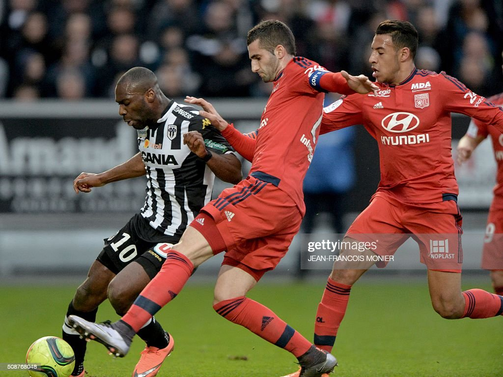 Angers' French forward Gilles Sunu (L) vies for the ball with Lyon's French midfielder Maxime Gonalons (C) and Lyon's French midfielder Corentin Tolisso (R) during the French L1 football match between Angers (SCO) and Lyon (OL), on February 6, 2016, in Jean Bouin Stadium, in Angers, northwestern France. AFP PHOTO / JEAN-FRANCOIS MONIER / AFP / JEAN-FRANCOIS MONIER